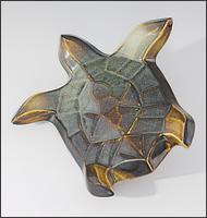 Image of Flying Sea Turtle sculpture in gold and green glaze, seen  from above, soaring to the viewers upper left.